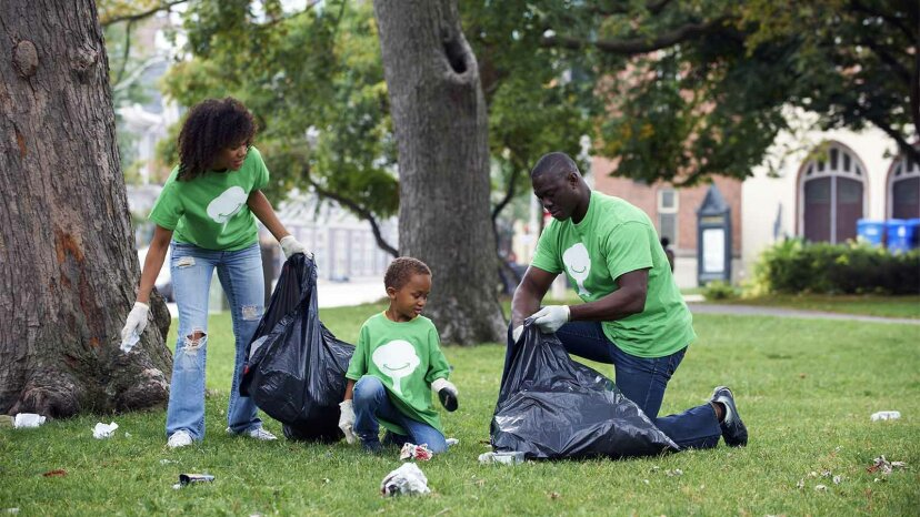 family cleaning up trash in park