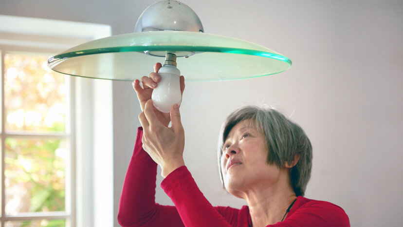 woman replacing light bulb