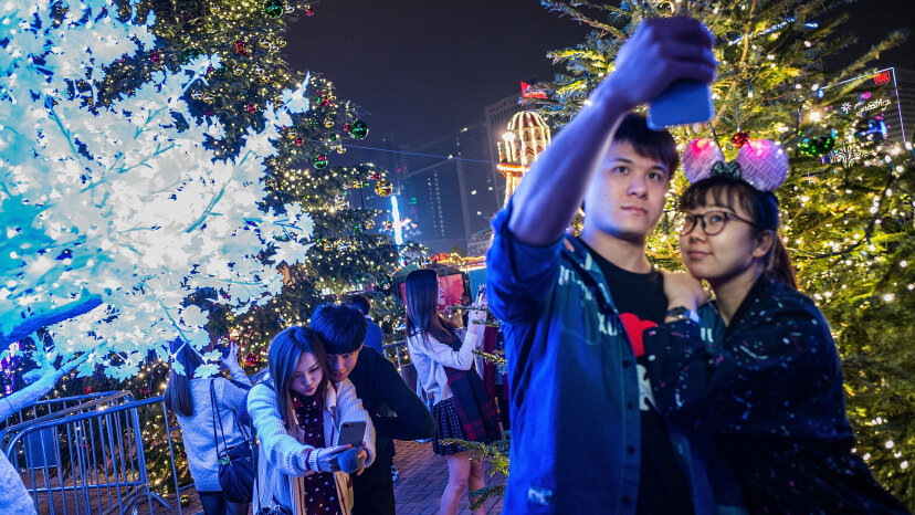 Young people take pictures in front of Christmas trees.
