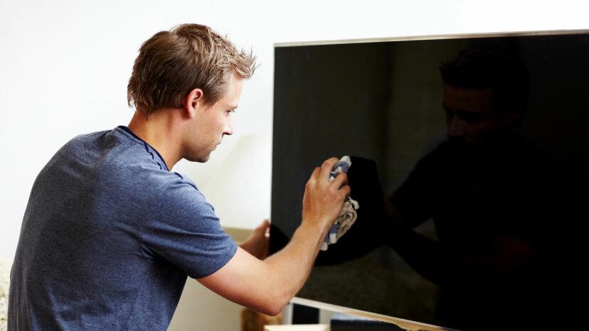 man cleaning flat screen tv