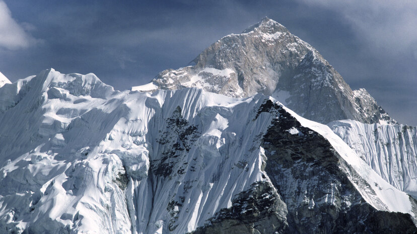Lower pressure at higher altitudes causes the temperature to be colder on top of a mountain than at sea level. Pictured is Mount Everest behind the mountain of Nuptse. Education Images/UIG via Getty Images