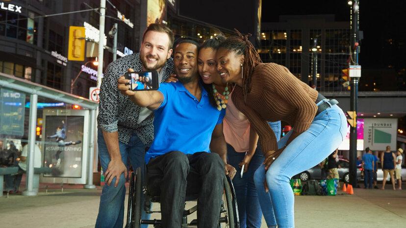 man in wheelchair with friends taking selfie
