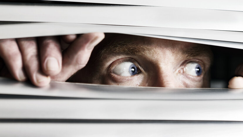 Terrified man looking out blinds