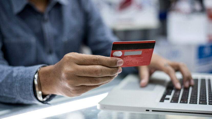 man with credit card on computer