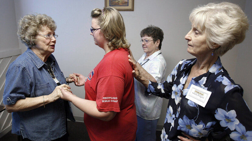 Volunteers lay their hands on a woman to pray for her wisdom, guidance and comfort at the Spokane Healing Rooms Ministries. Jeff T. Green/Getty Images