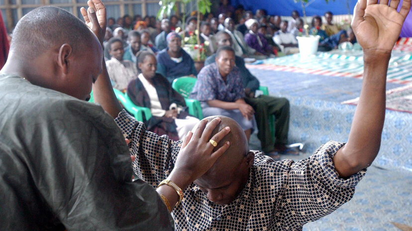 Kenyan Bishop John Nduati attempts to heal an HIV-positive man by laying a hand on him. AFP/Getty Images