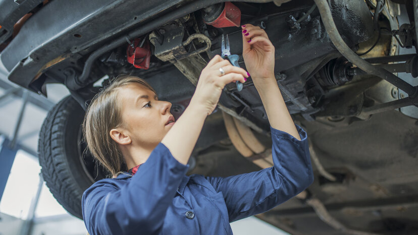 Mechanic inspecting a CV join on a car in auto repair shop