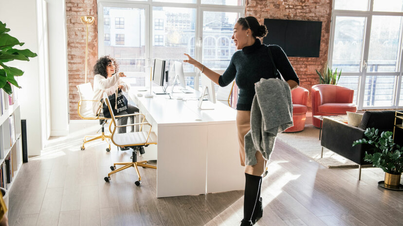 woman waving goodbye to another at office