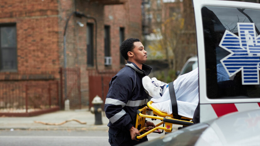 An EMT helps a patient into an ambulance