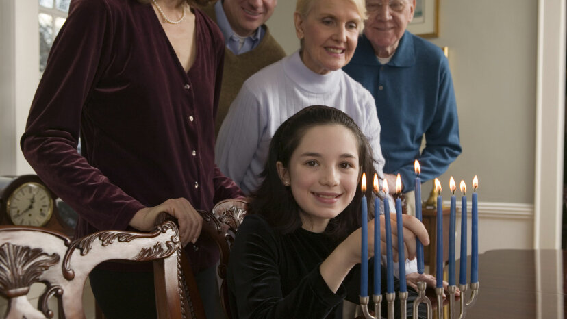 Little girl lighting menorah