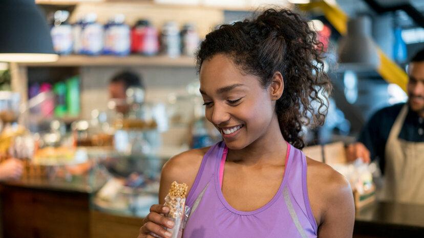 exerciser eating protein bar