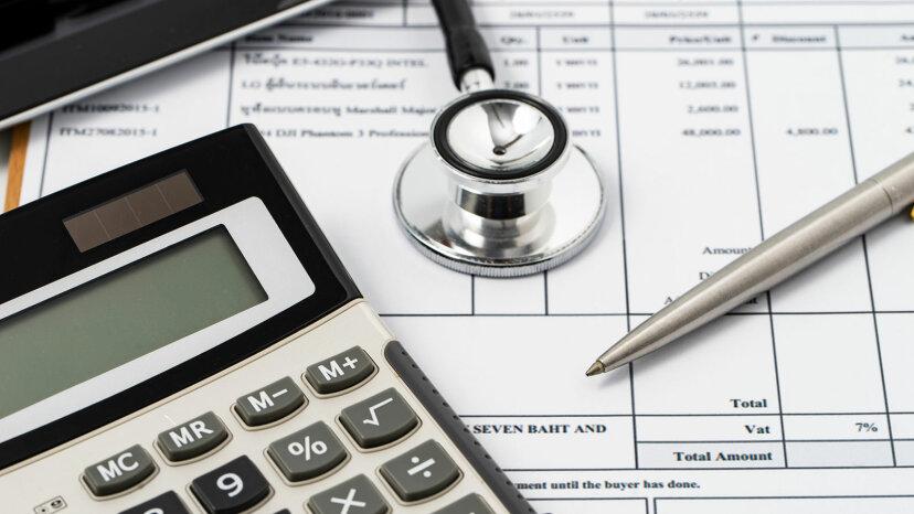 medical bills, stethoscope, calculator
