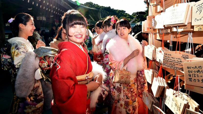 Twenty-year-old female tour guides dressed in traditional kimonos hang 'ema', or votive tablets, with their written wishes at Tokyo's Meiji shrine after attending a purification ceremony with a Shinto priest. Yoshikazu Tsuno/AFP/Getty Images