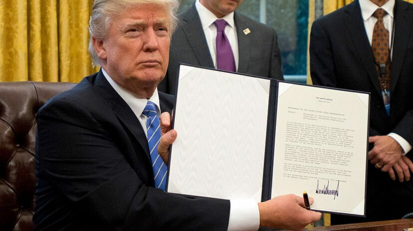 U.S. President Donald Trump shows the Executive Order withdrawing the US from the Trans-Pacific Partnership (TPP) after signing it in the Oval Office of the White House in Washington, D.C. on Jan. 23, 2017. Ron Sachs - Pool/Getty Images