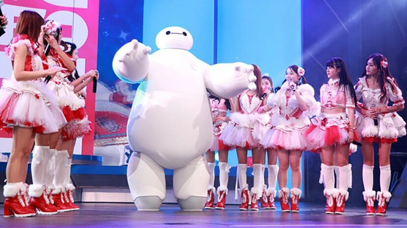 "An actor portraying the robot character Baymax from ""Big Hero 6"" appears onstage at a Shangai Disney resort with the pop group SNH48. VCG/Getty Images"