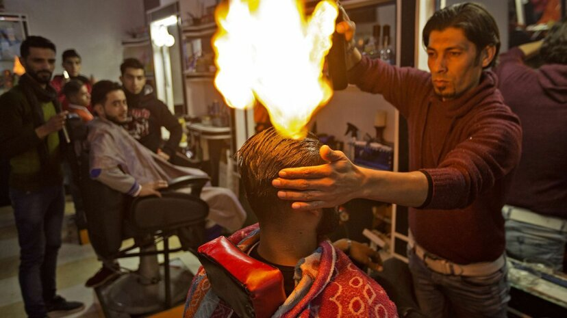Palestinian barber Ramadan Edwan uses fire to straighten the hair of one of his clients. MAHMUD HAMS/AFP/Getty Images
