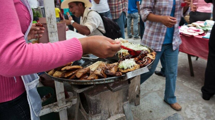 A woman prepares Mexican street food: mole enchiladas, fried tamales, fried tacos and quesadillas. Jacobo Zanella/Getty Images
