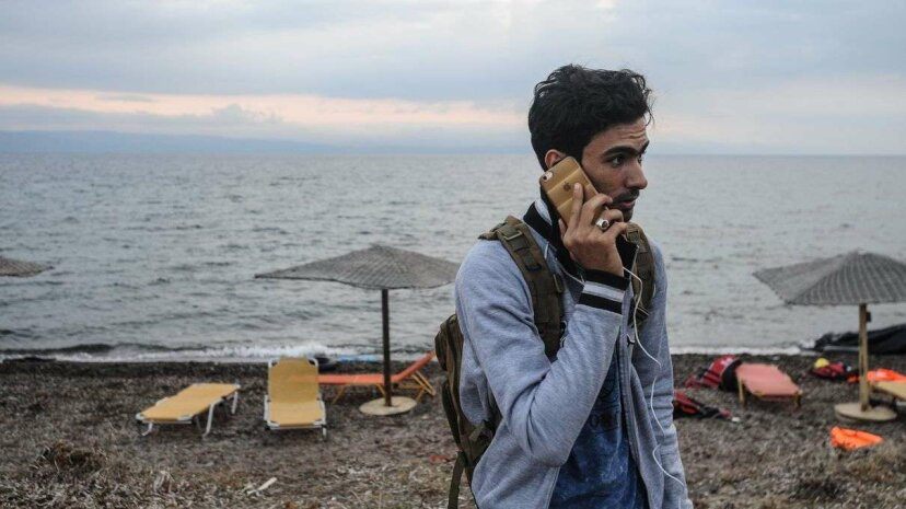 A refugee talks on a cell phone on the Greek island of Lesbos after crossing the Aegean Sea from Turkey on an inflatable dinghy. Thomas Campean /Anadolu Agency/Getty Images
