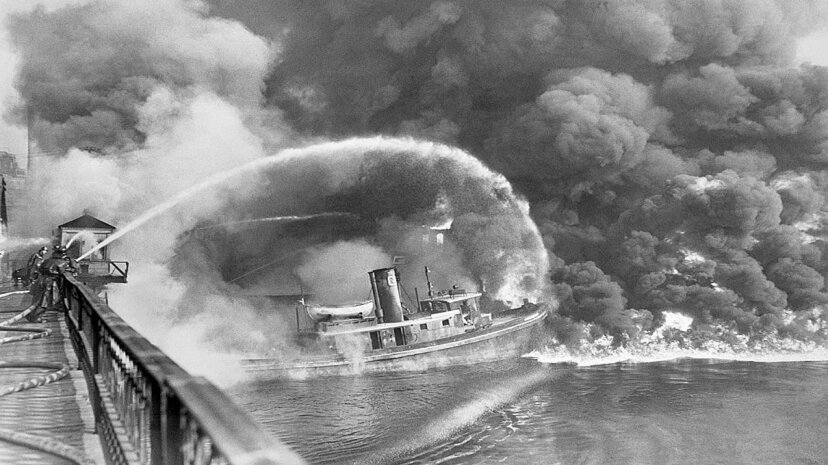 Firemen over the Cuyahoga River spray water on the tug Arizona while the river burns. Bettmann/Contributor/Getty