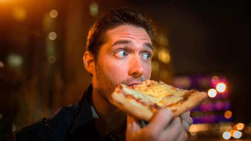 If that guy were following time-restricted eating, he wouldn't be indulging in that late-night slice. Steven Prezant/Image Source/Getty