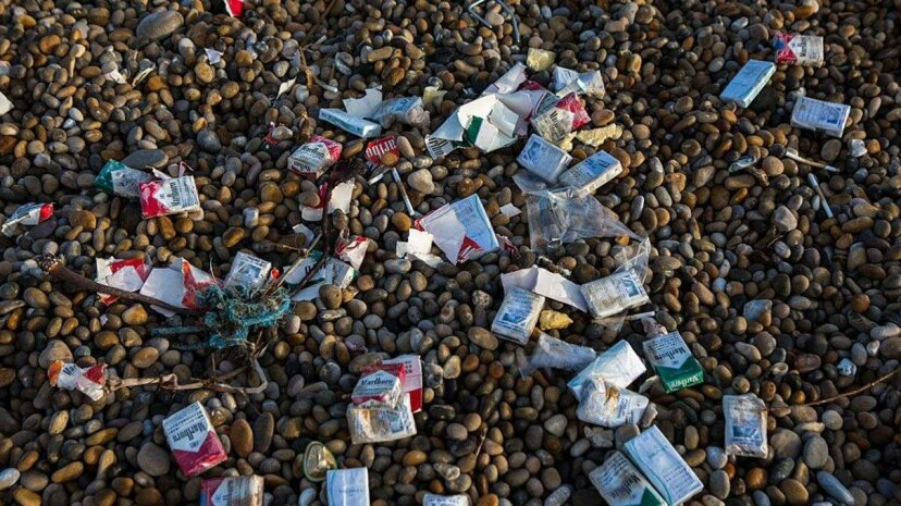 Cigarette packets from a container ship accident wash up on Chesil Beach in Dorset, England. : Andrew Aitchison/Getty Images