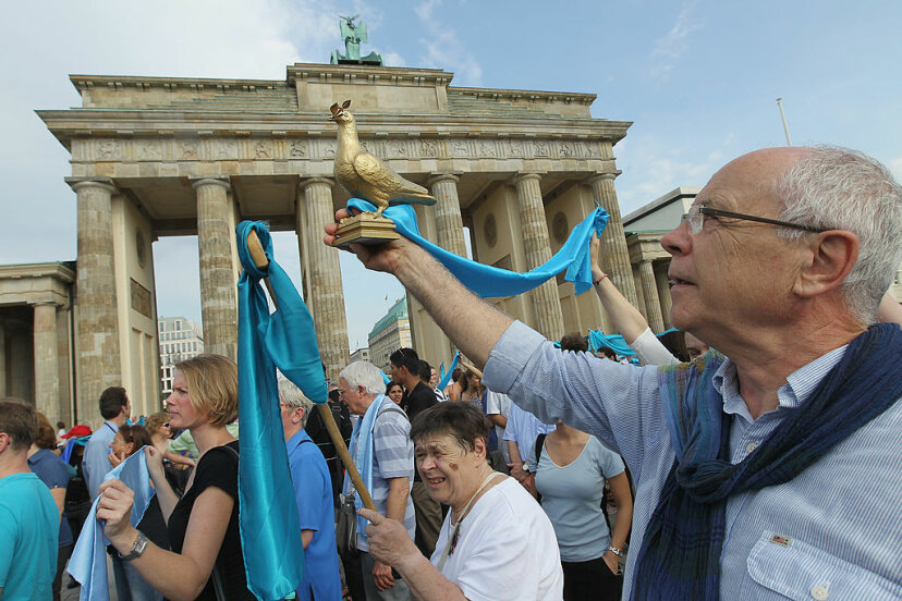Peace activists hold up blue ribbons and a sculpture of a peace dove during an interfaith commemoration of the 10th anniversary of the 9/11 terror attacks in front of the Brandenburg Gate on Sept. 11, 2011, in Berlin. Sean Gallup/Getty Images