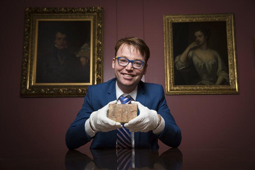 professor holding mesopotamian tablet
