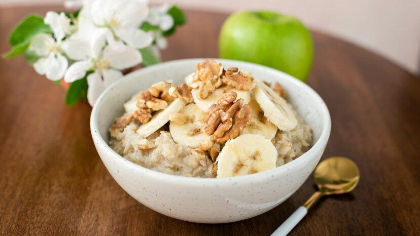 Oatmeal porridge with banana and walnuts in bowl.