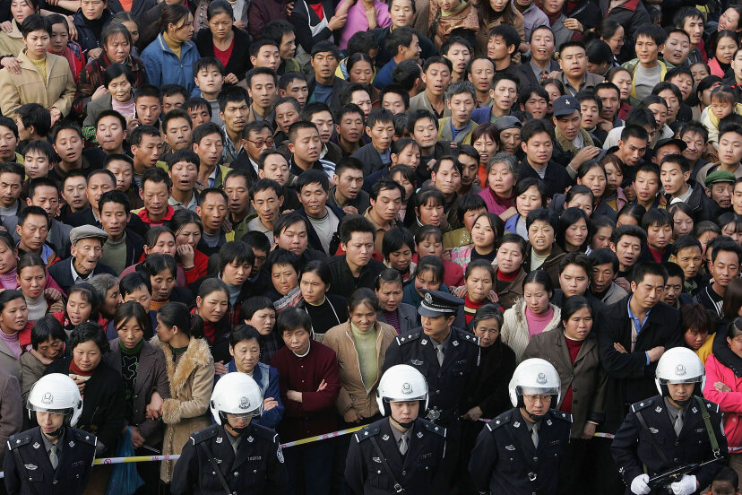 More than 10,000 residents of Chongqing, China, watch the public sentencing of four murderers as part of a campaign by local authorities to show their determination to crack down on surging crimes in 2004. China Photos/Getty Images