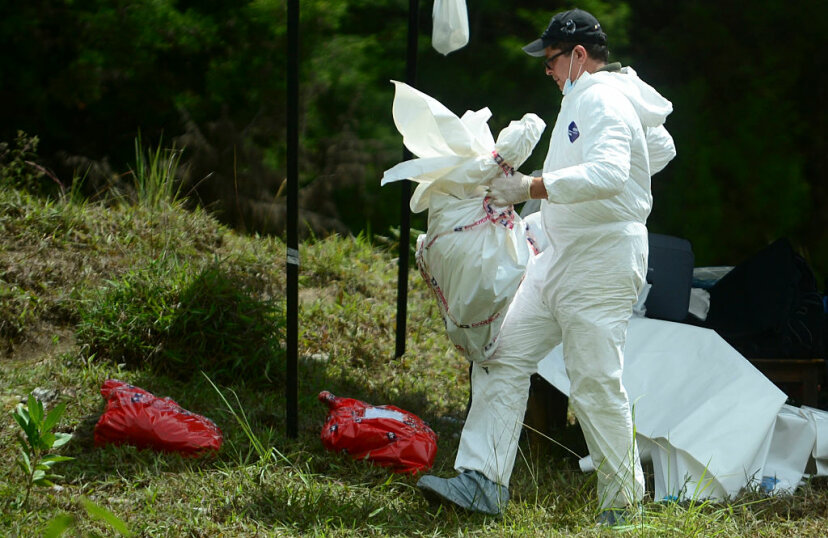 "Colombian police inspect corpses found in a mass grave at a farm in Guarne municipality in a case involving another serial killer, in 2016. Luis Garavito reportedly killed 300 people ""for pleasure"" in the 1990s. RAUL ARBOLEDA/AFP/Getty Images)"