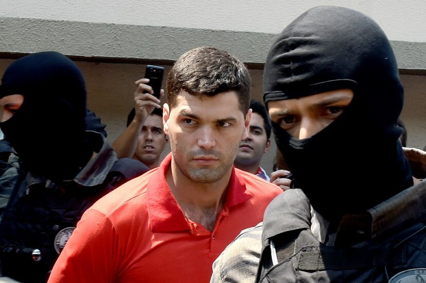 Tiago Gomes da Rocha (C), suspected of killing 39 people, is escorted by police officers at the Department of Security, a day after his arrest in Goiania in the state of Goias, Brazil, on Oct. 16, 2014. EVARISTO SA/AFP/Getty Images