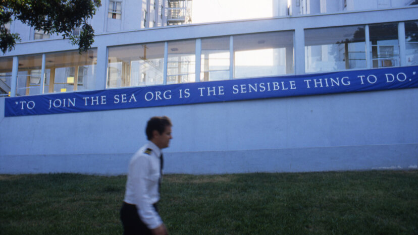 A member of the 'Sea Org' walks by a sign outside the Church of Scientology Los Angeles on Sunset Boulevard. Michael Montfort/Michael Ochs Archives/Getty Images