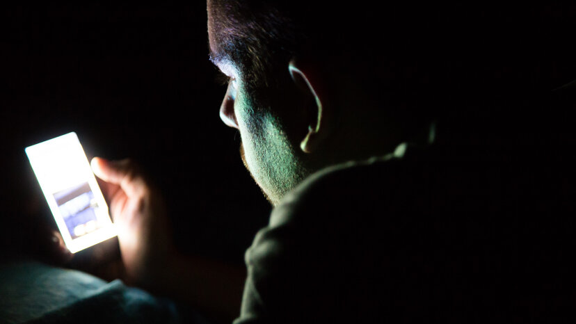 Man looking at phone in dark