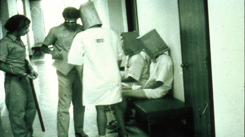 With bags over their heads, the prisoners wait on their parole hearing. PrisonExp.org