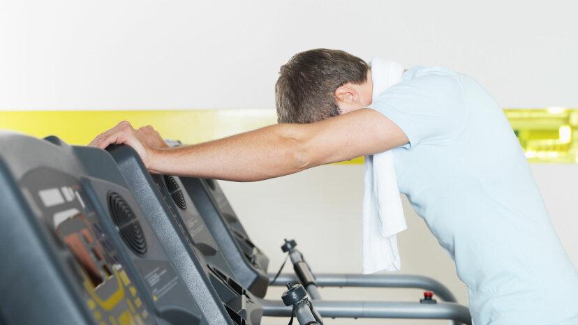 man standing over treadmill