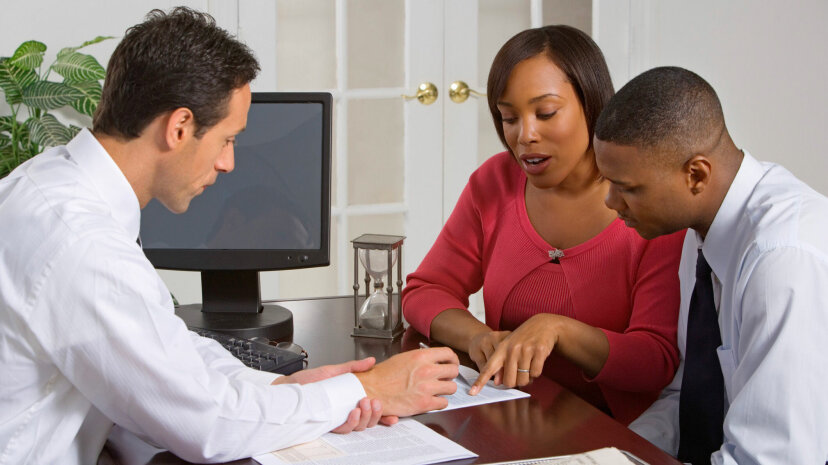 Businessman discussing paperwork with couple