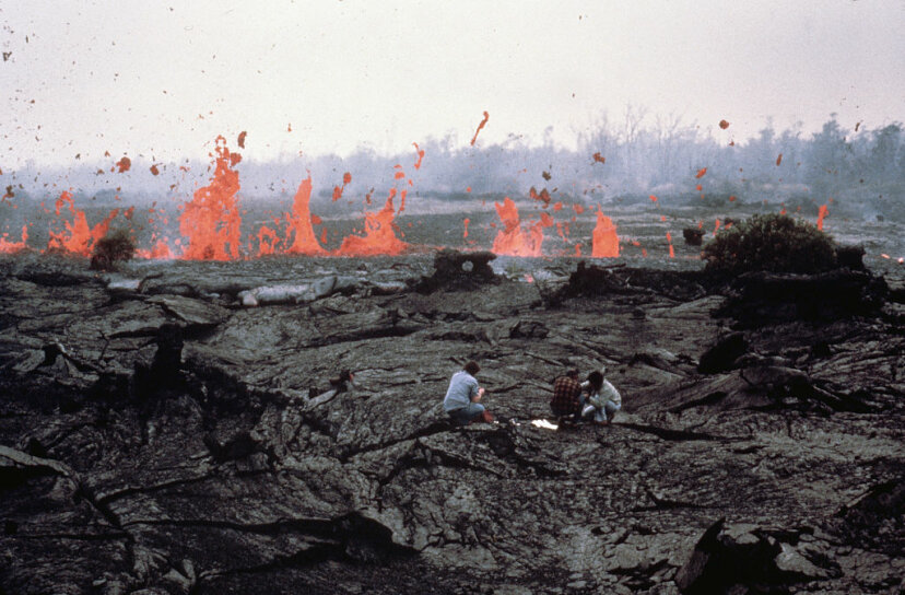 scientists in front of a lava flow