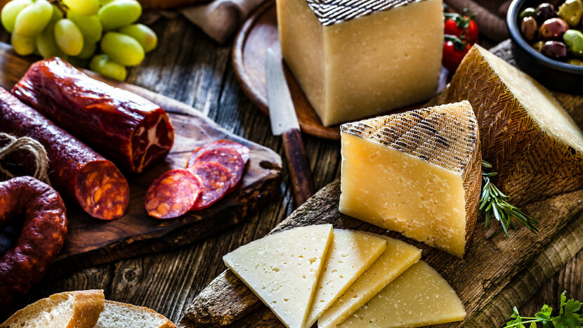 Manchego cheese pieces surrounded by Spanish chorizo, olives, bread slices and grapes.