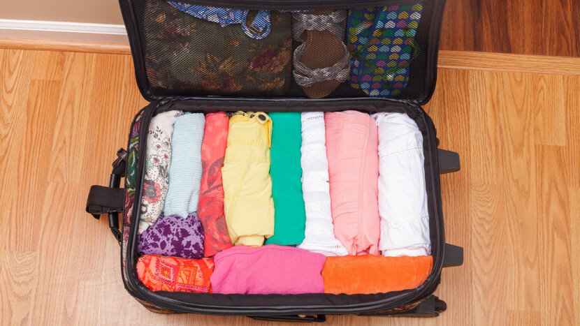 A suitcase with women's clothing packed by rolling the clothing,