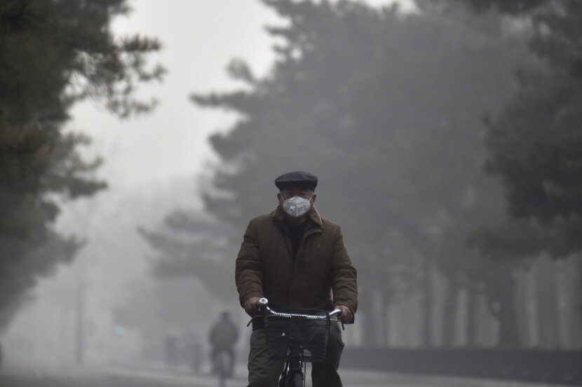 a man rides a bicycle in polluted air