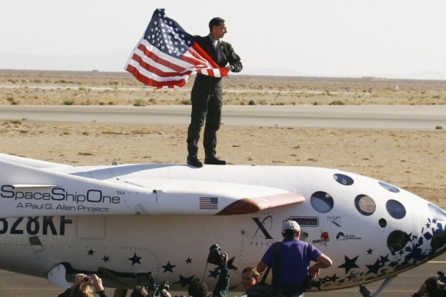 Pilot Brian Binnie holds an American flag after SpaceShipOne won the $10 million dollar Ansari X Prize. Awards like this can reinforce commercial space development. © Gene Blevins/LA Daily News/Corbis