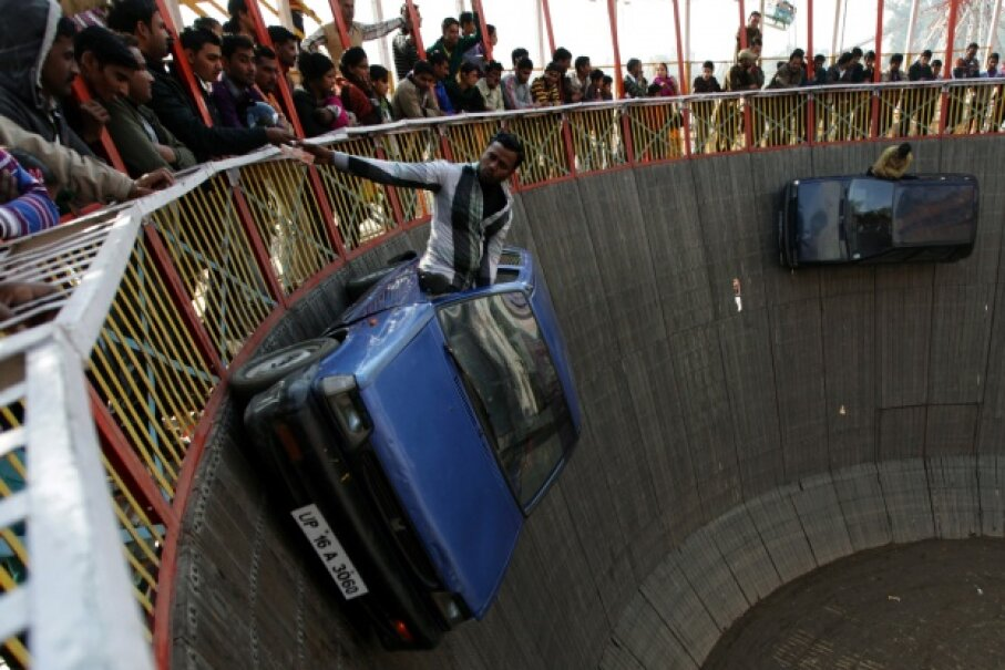 Indian performers ride in cars inside a makeshift wooden cylindrical 'Wall of Death' structure, during the annual farmers fair at Shama Chak Jhiri, some 22kms from Jammu.