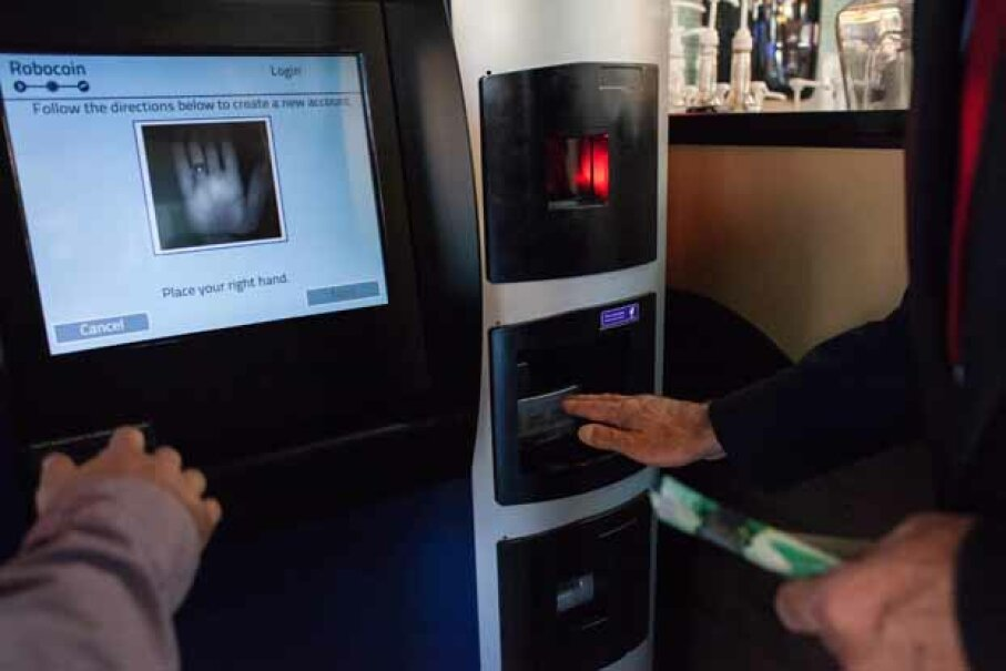 A user learns how to scan his palm to ensure that he cannot exchange more than $1,000 in a single day on the world's first bitcoin ATM at Waves Coffee House in Vancouver, B.C., in 2013. David Ryder/Getty Images