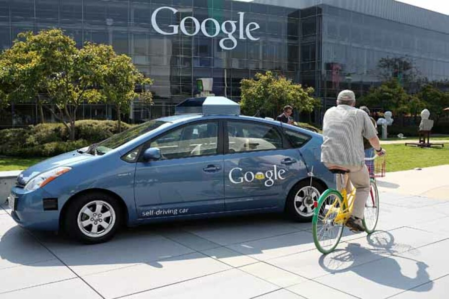 A bicyclist rides by a Google self-driving car at the Google headquarters in Mountain View, Calif. in 2012. Justin Sullivan/Getty Images