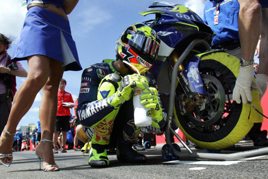 Valentino Rossi of Italy kneels next to his motorbike prior to the start of the German motorcycling Grand Prix at the Sachsenring in Hohenstein-Ernstthal. (UWE MEINHOLD/AFP/Getty Images)