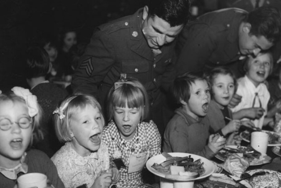 Soldiers serve children Thanksgiving dinner during World War II, around the time the U.S. Congress declared Thanksgiving an official holiday. Davis/Topical Press Agency/Getty Images