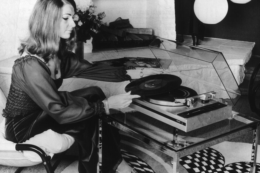 A model demonstrates the then-innovative automatic turntable at an electronics show in 1974. The turntable placed the pick-up on the record, lifted it off when it reached the end of the side and stopped the motor. Madina Gajimuradova /EyeEm/Getty Images