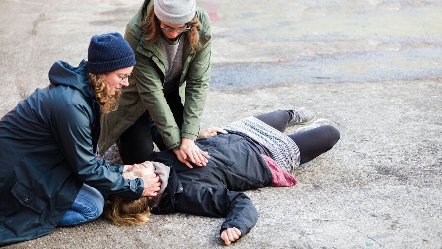 Two women perform CPR on another woman