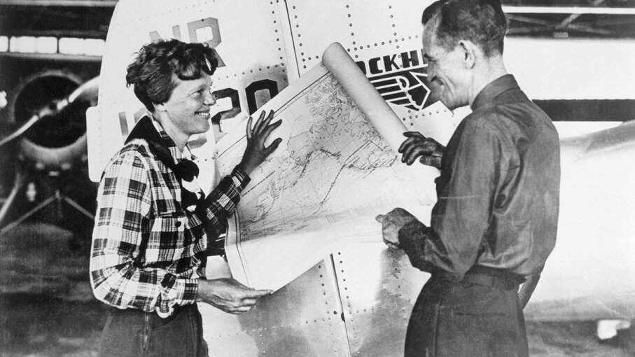 Pilot Amelia Earhart and her navigator Fred Noonan hold a map of the Pacific that shows the planned route of what became their final flight. Bettmann Archive/Getty Images