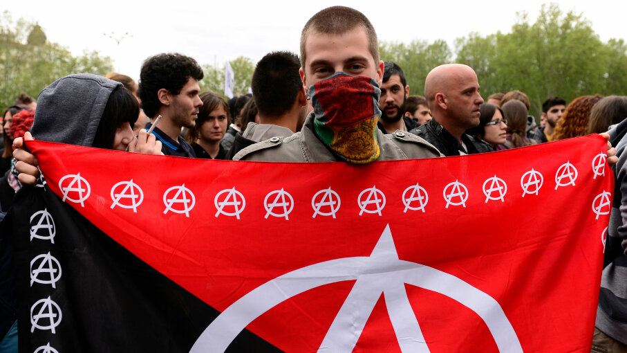 A masked demonstrator displays an anarchy flag close to the blocked street leading to Spain's parliament during an anti-government demonstration in Madrid in 2013. JAVIER SORIANO/AFP/Getty Images
